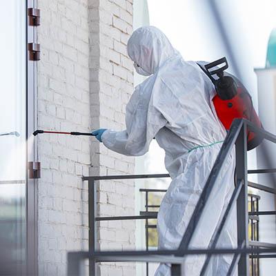 Produkt biobójczy w użyciu poprzez pracownika w pełnym kombinezonie.